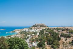 Distant view at Lindos Town and Castle with ancient ruins of the Acropolis on sunny warm day. Island of Rhodes, Greece. Europe.  stock photo