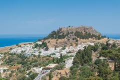 Distant view at Lindos Town and Castle with ancient ruins of the Acropolis on sunny warm day. Island of Rhodes, Greece. Europe.  royalty free stock image
