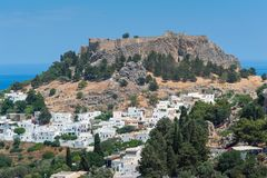 Distant view at Lindos Town and Castle with ancient ruins of the Acropolis on sunny warm day. Island of Rhodes, Greece. Europe.  royalty free stock photos