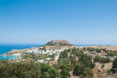 Distant view at Lindos Town and Castle with ancient ruins of the Acropolis on sunny warm day. Island of Rhodes, Greece. Europe.  royalty free stock photo