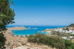 Distant view at Lindos Town and Castle with ancient ruins of the Acropolis on sunny warm day. Island of Rhodes, Greece. Europe.  stock photography