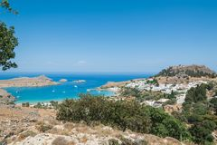 Distant view at Lindos Town and Castle with ancient ruins of the Acropolis on sunny warm day. Island of Rhodes, Greece. Europe.  stock photos