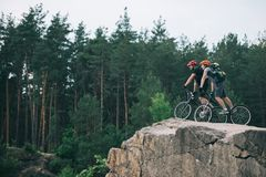 Distant view of male extreme cyclists in protective helmets riding on mountain bicycles on rocky cliff. In forest royalty free stock images