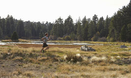 Distant view of man running in nature near a lake Stock Photo