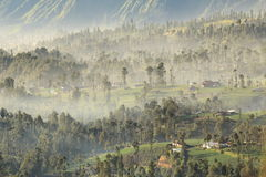 Distant view of a misty village on cliff Royalty Free Stock Images