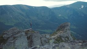 Distant view of a risky female photographer with backpack standing on the high rocky ledge overlooking the green stock video footage