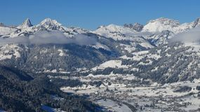 Distant view of Saanen and snow covered mountains Stock Photo