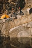 distant view of two male travelers standing with mountain bikes near tent on rocky cliff royalty free stock photos