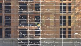 Construction Workers Installing Plywood Walls on a New Building. From a distant view, two workers are shown installing plywood walls on a new, tall building stock video