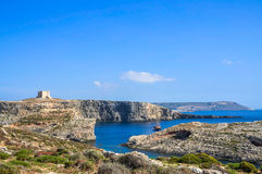 Distant views of a boat and Saint Mary`s Tower in the Island of Comino, Malta. At only 3.5 square kilometres, the Island of Comino is virtually uninhabited – Stock Images