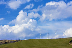 Distant wind-farm and cloudscape. Distant hillside wind-farm and cloudscape background stock images