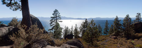 Distant Yacht on Lake Tahoe. Panoramic photo of a distant yacht shimmering in the reflected rays of the sun on lake Tahoe with mountains in the background and stock images