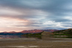Distant Yukon mountains glowing in sunset light Stock Photos