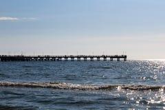 Distante no horizonte está um cais marítimo para andar imagens de stock