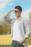 distanza che osserva i giovani dell'uomo Fotografia Stock Libera da Diritti