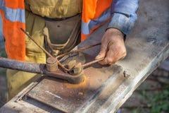 Distanziatori di piegamento del lavoratore per i tondi per cemento armato in una posta concreta 3 Immagine Stock