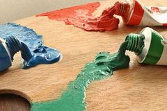 Distemper colours on the palette. Three hue on the wooden pallete stock photos