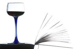Distendendosi con un libro e un vino rosso. Immagini Stock