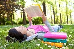 Distendendosi in natura con il libro e la musica Immagini Stock