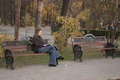Distendendosi in una sosta che legge un libro Immagini Stock Libere da Diritti