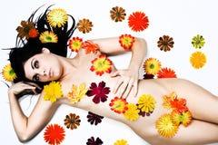 Distensione della giovane donna coperta in fiori Fotografia Stock