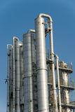 Distillation columns. At industrial plant or refinery against deep blue sky Stock Images