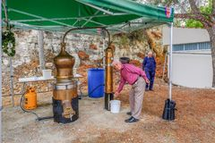 Distilling Zivania at a Cypriot festival. Arsos Village, Cyprus - October 8, 2017: Man testing Zivania from a working still at a village festival Stock Images