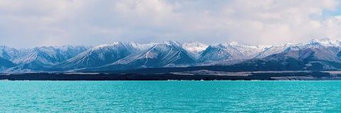 Distinctief Blauw Watermeer met Sneeuw Afgedekte Bergalpen op Achtergrond stock foto's
