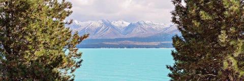 Distinctief Blauw Watermeer met Sneeuw Afgedekte Bergalpen op de Achtergrond stock afbeeldingen