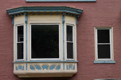 Distinctive Bay Window. A distinctive and ornate bay window on a building with a brick wall Stock Photos