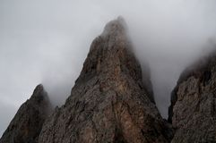Distinctive Mountain rock formation in fog. Distinctive Dolomite mountains in gardena valley / south tyrol Royalty Free Stock Photography