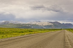 Distinctive mountains along the Dempster Highway. The Dempster Highway and distinctive bare eroded mountain ranges Stock Photo