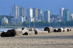 West Coast Beachfront. The distinctive Vancouver city skyline with sand and logs lining the beach along English Bay waterfront Stock Image