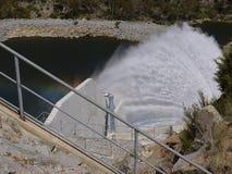Distinging water through a dam Stock Photo