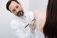 Distinguished enthusiastic doctor outlining the areas he correcting. Petite client. Handsome trained dedicated plastic surgeon putting marks on patients skin Stock Photo