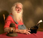 Distinguished  gentleman typing. Color photograph of an elderly bearded gentleman typing a letter on an old vintage typewriter Royalty Free Stock Photography