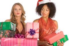 Distinzione dei regali di natale in mezzo alle donne immagini stock