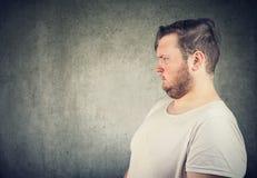 Distogliere lo sguardo robusto infastidito dell'uomo fotografia stock