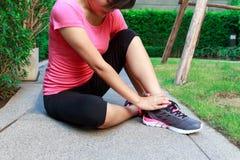 Distorsione sportiva della caviglia della donna mentre pareggiando o correndo al parco Immagini Stock