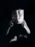 Distorted Childs Face. Girl holding a magnifier in front of face in yoga position Stock Images