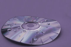 Distorted Disc II. A purple monochrome warped compact disc with water droplets Royalty Free Stock Image