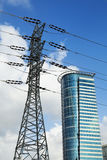 Pylon & Skyscraper. Distorted perspective view of a high-voltage electricity pylon makes it look taller than an office building behind it Stock Images