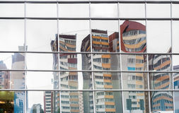 Distorted reflection of houses in mirror surface of facing of sh Royalty Free Stock Photos