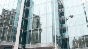 Distorted reflection of old building in modern office glass facade in Paris. Opposites concept Stock Photos