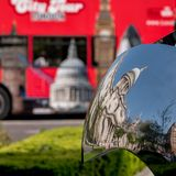 Distorted reflection of St Paul`s Cathedral, reflected in surface of mirror sculpture. Blurred red London bus in background. Distorted reflection of St Paul`s Royalty Free Stock Photography