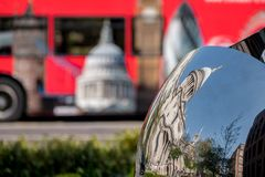 Distorted reflection of St Paul`s Cathedral, reflected in surface of mirror sculpture. Blurred red London bus in background. Distorted reflection of St Paul`s Stock Image
