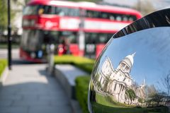 Distorted reflection of St Paul`s Cathedral, reflected in surface of mirror sculpture. Blurred red London bus in background. Distorted reflection of St Paul`s Royalty Free Stock Photos