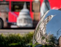 Distorted reflection of St Paul`s Cathedral, reflected in surface of mirror sculpture. Blurred red London bus in background. Distorted reflection of St Paul`s Stock Photos