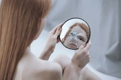 Distorted reflection of a woman. In a small, broken mirror Stock Photography