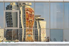 Distorted Reflections of buildings in the city in the stained-glass window. Painted building in reflecting windows Royalty Free Stock Photos